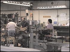 McNaughton and Gunn employees working on printing press